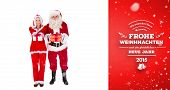 Santa and Mrs Claus smiling at camera offering gift against red vignette
