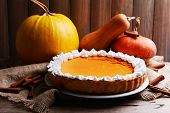 foto of pumpkin pie  - Composition of homemade pumpkin pie on plate and fresh pumpkins on wooden background - JPG