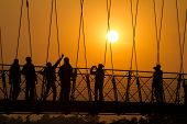 People silhouettes on the sunset on Lakshman Jhula bridge over Ganges in Rishikesh, India.