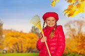 Portrait of beautiful smiling girl with rake