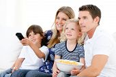 Smiling Family Watching A Film At Television