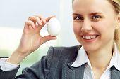 Smiling businesswoman holding white egg