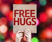 Free Hugs written on colorful background with defocused lights