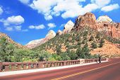 Zion National Park USA. Excellent with red asphalt road among the picturesque mountains of orange and red sandstone. Photographer in a black T-shirt and black jeans pictures of the spectacular scenery