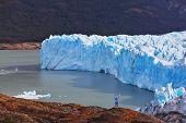 The woman - tourist admire the white-blue icy splendor. Giant lake Perito Moreno glacier