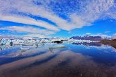 Cirrus clouds are beautifully reflected in the smooth water of the ocean lagoon. Yokulsarlon Glacial Lagoon in Iceland