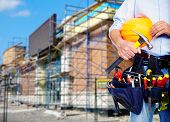 Worker with a tool belt over construction background.