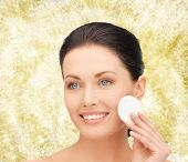 beauty, people and health concept - beautiful smiling woman cleaning face skin with cotton pad over yellow lights background