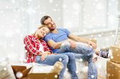 repair, moving in and people concept - smiling couple relaxing on sofa in new home