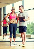 sport, fitness, lifestyle and people concept - smiling man and woman with scales and clipboard in gym