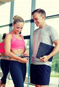 fitness, sport, exercising and diet concept - smiling young woman with measuring tape and personal trainer in gym