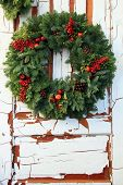 Christmas wreath of  evergreen and red holly berries against a vintage wooden door.