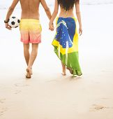 Young attractive couple walking on beach holding hands