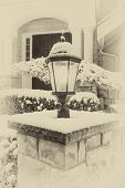 stock photo of lamp post  - Vintage concept of lamp post with snow on top in front of home - JPG