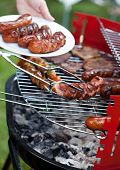 stock photo of frazzled  - Closeup of delicious sausages prepared on grill - JPG