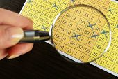 foto of lottery winners  - Female hand with magnifier analyzing lottery ticket - JPG