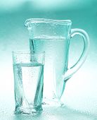 stock photo of pitcher  - Glass pitcher and glass of water on blue background - JPG