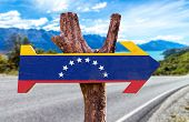 stock photo of canaima  - Venezuela Flag wooden sign with road background - JPG