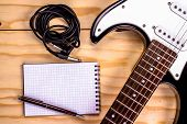 image of sounding-rod  - electric guitar and memo pad on wooden table - JPG