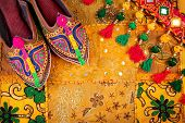 stock photo of flea  - Colorful ethnic shoes and gipsy belt on yellow Rajasthan cushion cover on flea market in India - JPG