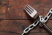 image of food chain  - Fork attached with metal chain on wooden background - JPG