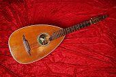 picture of string instrument  - vintage lute string instrument on red velvet background - JPG