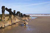 picture of breaker  - Wooden wave breakers on beach at seaside resort environmental preservation issues - JPG
