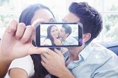 stock photo of cuddle  - Hand holding smartphone showing against attractive couple cuddling on the couch - JPG