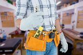 picture of pliers  - Technician with tool belt around waist holding pliers against workshop - JPG