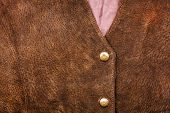 picture of vest  - Fragment of a brown suede vest with some buttons - JPG