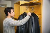 picture of wardrobe  - Serious Handsome Young Man Hanging his Black Coats at his Wardrobe Inside his Room - JPG