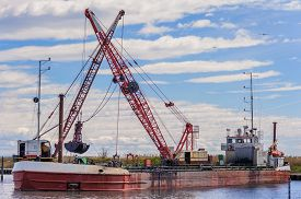 stock photo of dredge  - Small dredge marine which is cleaning a navigation channel - JPG