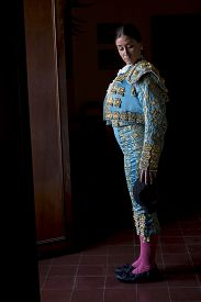 image of bullfighting  - Woman Bullfighter in hotel room before going to the plaza de toros in Seville Spain on a black background