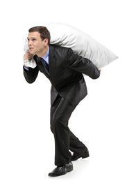 stock photo of heavy bag  - Full length portrait of a businessman carrying a money bag isolated against white background - JPG