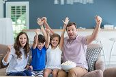 Smiling family cheering while watching tv in living room at home poster