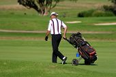 Golf player walking with the golf pull cart