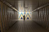 Man walking alone through tiled road underpass