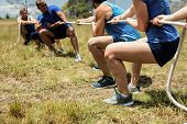 People playing tug of war during obstacle training course in boot camp poster