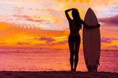 Hawaii surfer woman at sunset with surfboard on beach. Surf lifestyle. poster