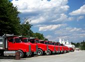 pic of fleet  - Fleet of bright red trucks in industrial yard - JPG