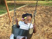 foto of passy  - Child on swing in park with pacifier - JPG