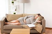 pregnancy, rest, people and expectation concept - happy pregnant woman sleeping on sofa at home poster