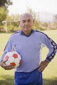 Senior Chilean soccer player holding soccer ball poster