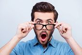 Wow! Really?! Surprised Young Handsome Man With Opened Mouth Touching Glasses poster