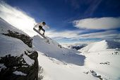Snowboarder riding off cliff with deep blue sky in background