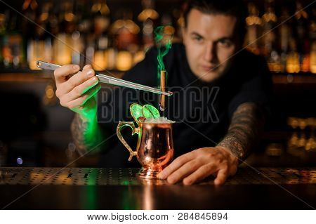 Male Bartender Adding To A
