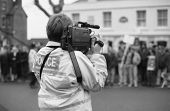 TENTERDEN, ENGLAND - DECEMBER 26: A police officer films anti hunt protestors at the Boxing Day meet of the Ashford Valley Hunt in the High Street on December 26, 1992 at Tenterden, Kent.