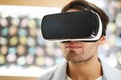 Young Man With Vr Headset Watching Curious Video Or Traveling In Virtual World At Leisure poster