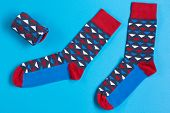 Two Multi-colored Socks Are Located On A Blue Background, A Folded Sock Lies Next To It poster