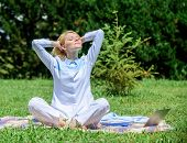 Girl Meditate On Rug Green Grass Meadow Nature Background. Woman Relaxing Practicing Meditation. Eve poster